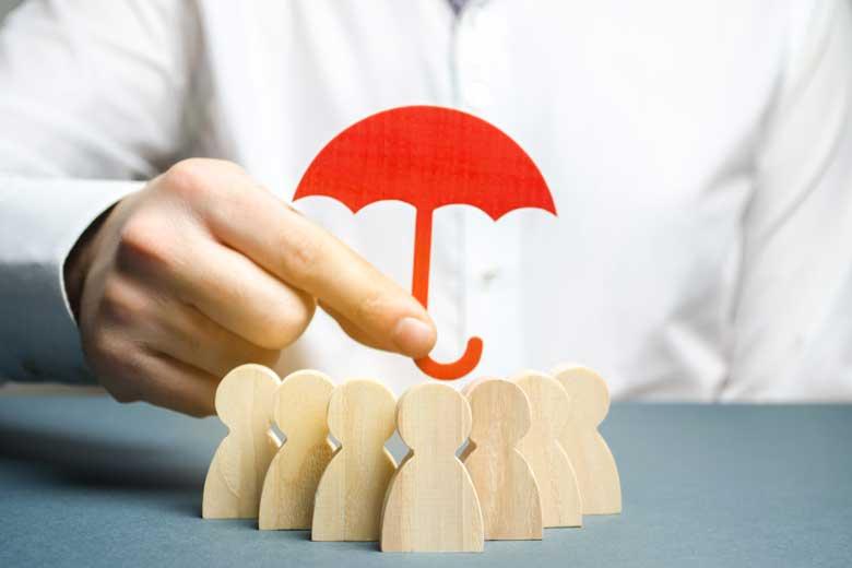 Eine Hand hält einen Regenschirm über eine Gruppe von Holzfiguren.