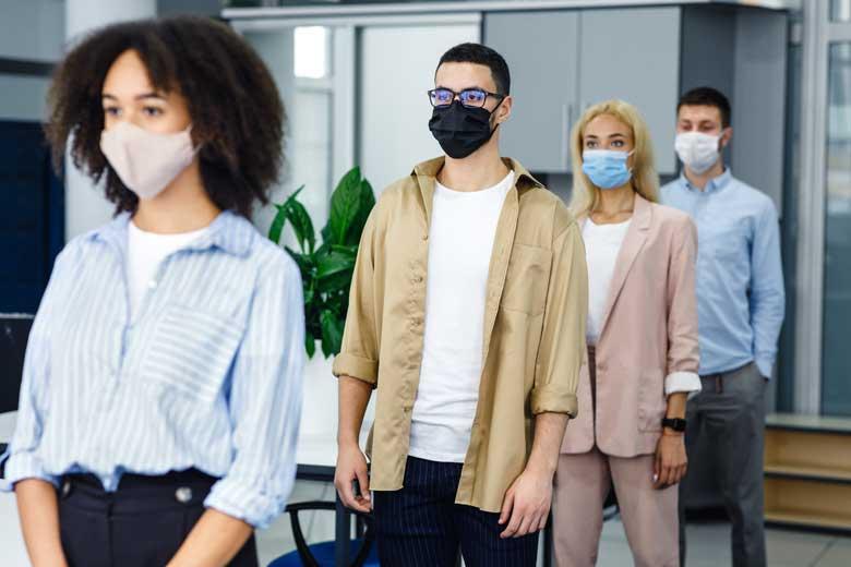 Maskierte Menschen stehen waehrend des zweiten Lockdown schlange