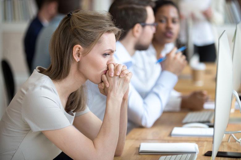 Sehr gute Mitarbeiter sitzen frustriert am Arbeitsplatz