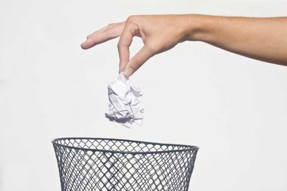 Eine Hand hält ein zerknülltes Anschreiben über einem Papierkorb.