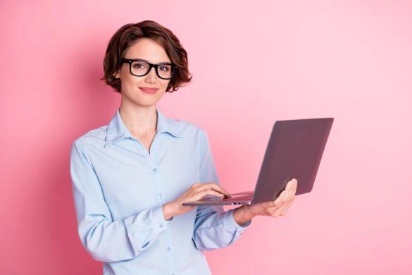 Mitarbeiterin des HR-Managements mit Laptop vor rosa Wand
