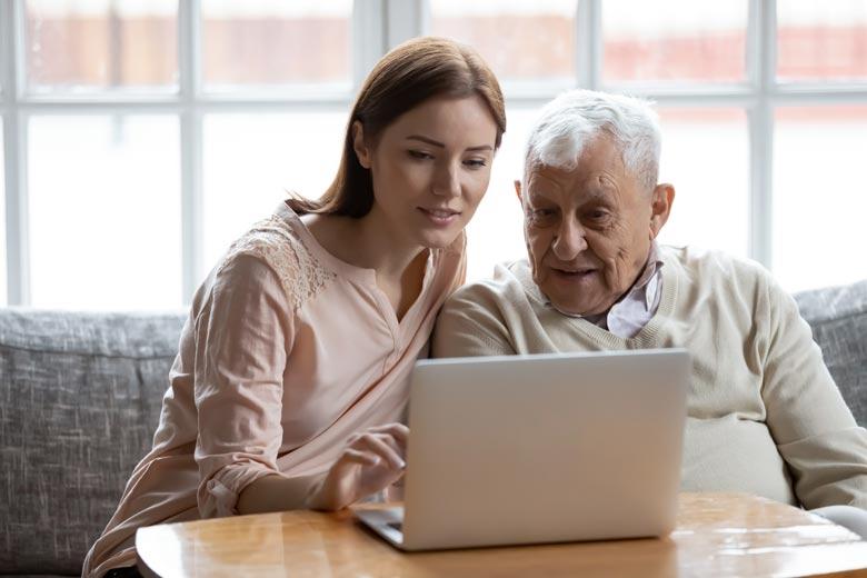 Eine Gruppe Senioren schaut gemeinsam auf ein Smartphone