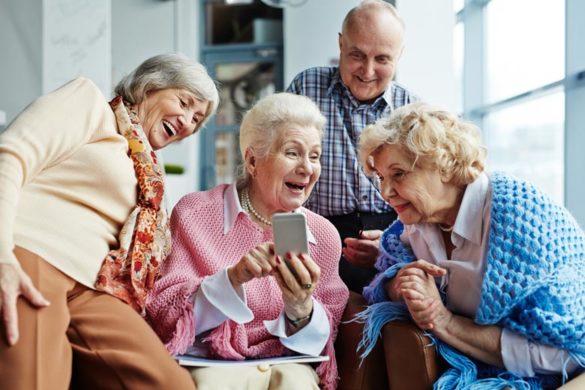 Senioren im Internet: Eine Gruppe Senioren schuat gemeinsam amuesiert auf ein Samrtphone