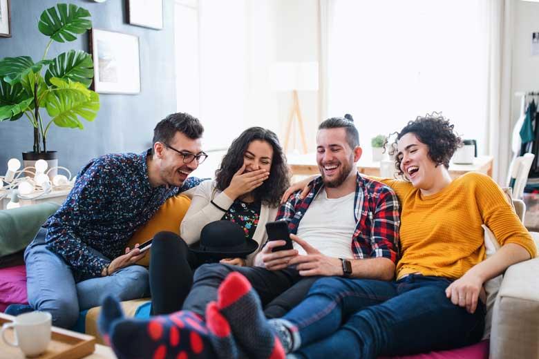 Junge Menschen auf dem Sofa lachen über witzigen Content auf dem Smartphone