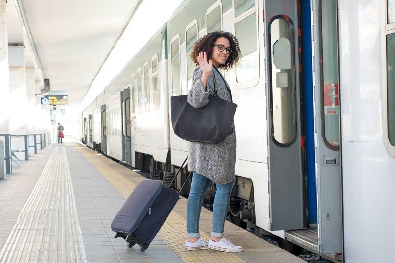 Junge Frau steigt in einen Zug und winkt sich zum Abschied