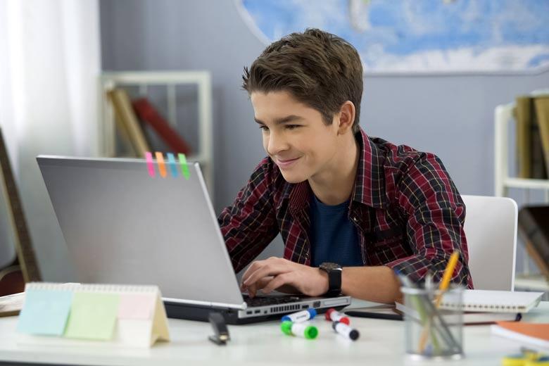 Junger Digital Native sitzt während des Home Schoolings am Laptop