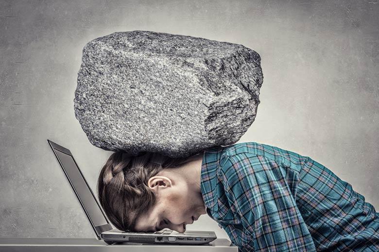 Unter Druck im Studium: Studentin wird von einem Felsen auf einen Laptop gedrückt.