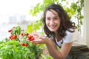 Junge Frau ist stolz auf ihre Balkonbepflanzung