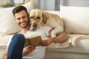 Junger Mann mit Hund beim Lesen