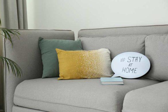 Stay at Home Schild auf einem Sofa