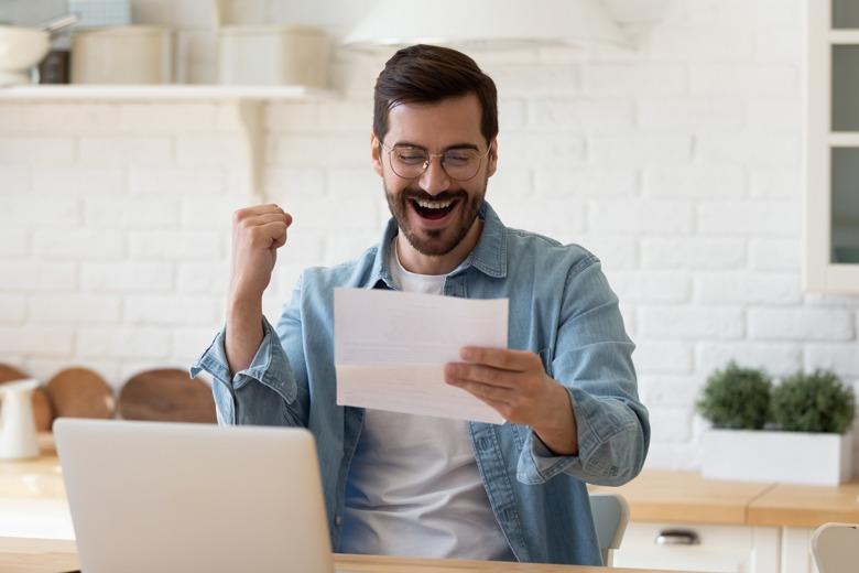Junger Mann freut sich ueber positive Bewerbung ohne Anschreiben