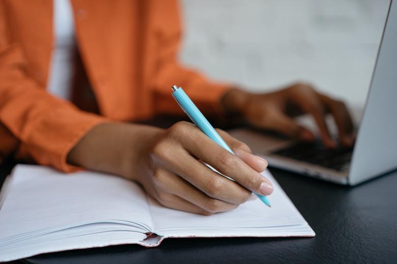 Frau sitzt vor Laptop und macht notizen waehrend Persoenlichkeitstest