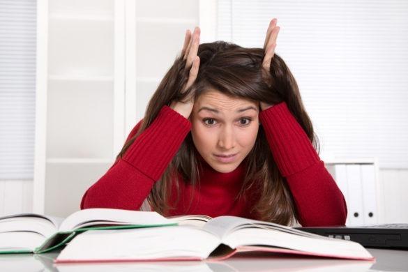 Studentin sitzt verzweifelt vor aufgeschlagenen Buechern hat Versagensangst kurz vor Studienabschluss